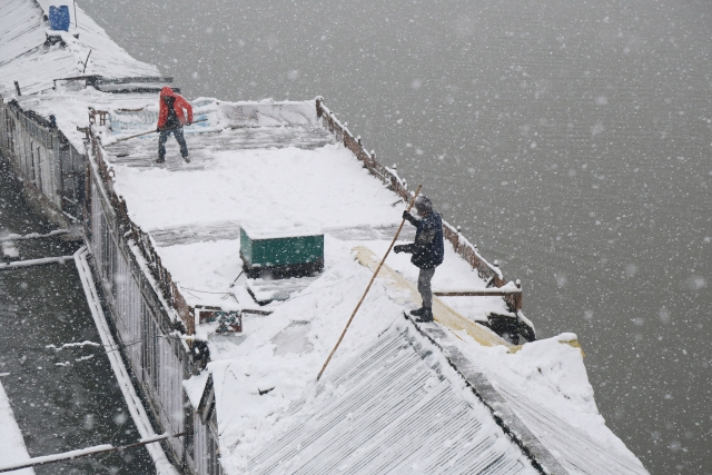 Boat men clear snow from their houseboat  amid heavy snowfall in Srinagar.