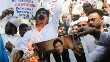 Indian muslims burn posters of Pakistani prime minister Imran Khan, center, and Jaish-e-Mohammed leader Masood Azhar, during a protest against attack on a paramilitary convoy in Kashmir that killed at least 40 CRPF jawaans.