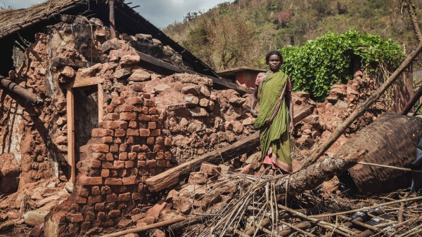 A woman stands in front of her broken house.