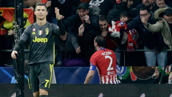 Diego Godin celebrates in the background as Cristiano Ronaldo cuts a dejected figure during Juventus' 2-0 defeat at Atletico Madrid in the UEFA Champions League.