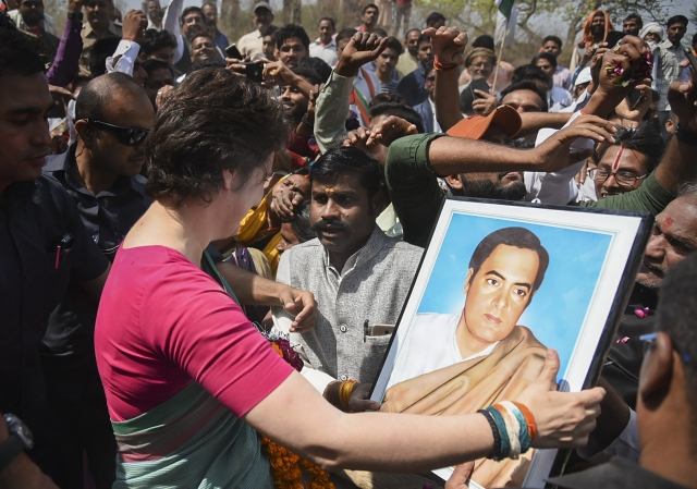 Congress' eastern Uttar Pradesh in-charge Priyanka Gandhi Vadra holds a portrait of her father, former prime minster Rajiv Gandhi as she starts her party's campaign for the Lok Sabha elections in UP, from Manaiya Ghat in Kachnar tehsil of Prayagraj.