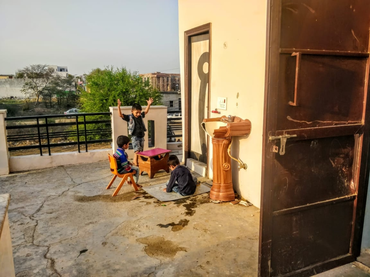 Kids of the house play behind the door that protected Daanishtha from the mob.