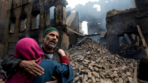A Kashmiri woman comforts a wailing relative after his house was destroyed in a gunbattle in Tral village, south of Srinagar, on Tuesday, 5 March.