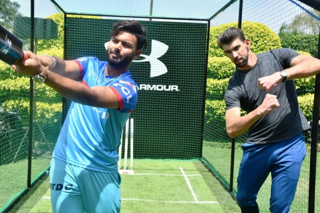 Indian cricketer Rishabh Pant shows Michael Phelps how to swing a bat.
