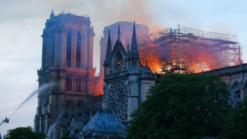 A firefighter tackles the blaze as flames and smoke rise from Notre Dame cathedral as it burns in Paris.