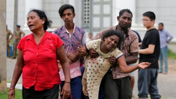 Relatives of a blast victim grieve outside a morgue in Colombo, Sri Lanka on Sunday, 21 April 2019.