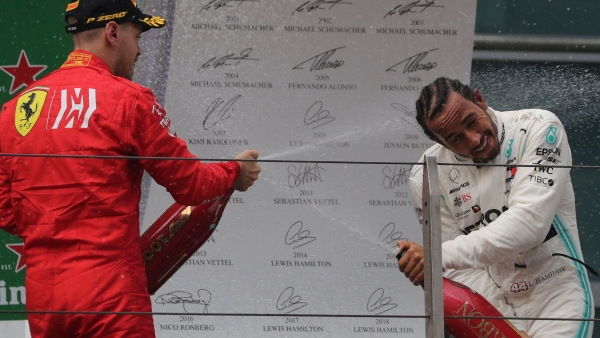 Lewis Hamilton of Britain is sprayed with champagne by  Sebastian Vettel during the award ceremony after the Chinese Formula One Grand Prix.