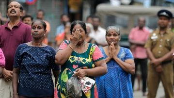 Sri Lankan Catholics pray standing on a road as they attend a brief holy service marking the seventh day of the Easter Sunday attacks near the remains of St Anthony's Church in Colombo, Sri Lanka, on Sunday, 28 April, 2019.