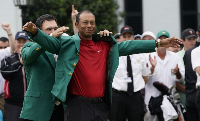 Patrick Reed helps Tiger Woods with his green jacket after Woods won the Masters golf tournament Sunday, April 14, 2019, in Augusta, Ga.