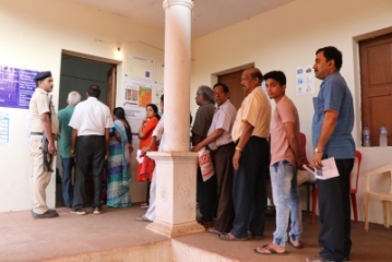 Verem, North Goa: People stand in a queue to caste their vote for Lok Sabha elections at a polling booth in Verem, North Goa on April 23, 2019. (Photo: IANS)
