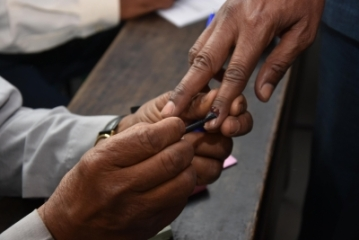 A polling official applies indelible phosphorus ink on the fore finger of a voter. (File Photo: IANS)