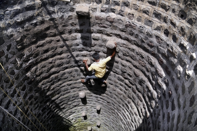 A villager climbs down a well to fetch water, in a wada of Dhasai village in Murbad taluk of Thane district. Dhasai. Some reports suggest that authorities are not supplying water to the village regularly, making the excuse of model code of conduct due to ongoing Lok Sabha elections.