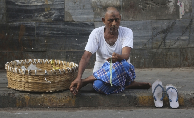 A Muslim labourer holds a prayer bead as he waits for a work on a pavement in Mumbai.