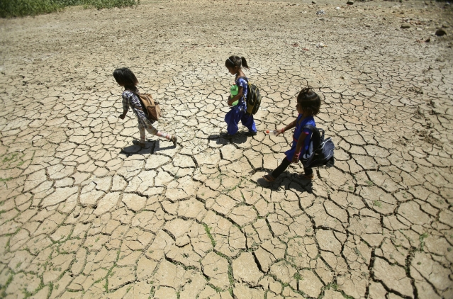 Children returning from school walk through a dried pond on a hot summer day on the outskirts of Jammu.