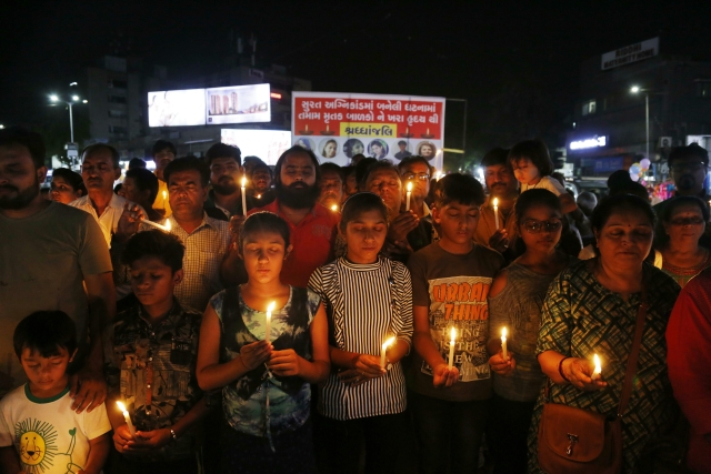 Mourners attend a candlelight march in tribute to the victims of a deadly fire in Surat, in Ahmadabad.
