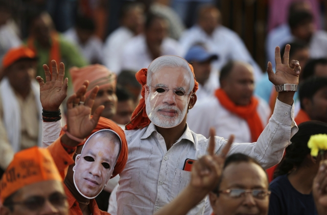 Bharatiya Janata Party (BJP) supporters wear masks of Prime Minister Narendra Modi and Uttar Pradesh Chief Minister Yogi Adityanath during an election rally in Prayagraj, India, Monday, 29 April 2019.