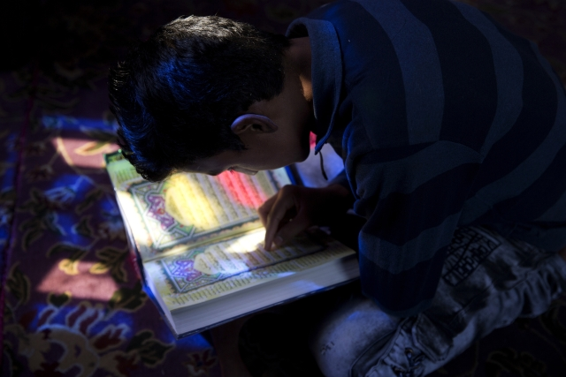 A Kashmiri boy reads verses from the Holy Quran inside the shrine of Sufi saint Shiekh Abdul Qadir Jeelani during the holy fasting month of Ramadan in Srinagar.