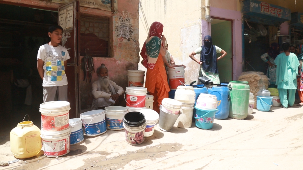 Women wait in the heat to fill water from the water tanker.
