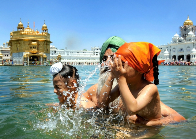 Sikh devotees take a dip in the holy Sarovar  at the Golden Temple  on the occasion of 'Gurta Gaddi Diwas' of Guru Hargobind Ji, the sixth Sikh Guru, in Amritsar.