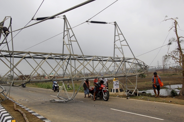 Commuters ride past damage caused by Cyclone Fani in Odisha. A mammoth evacuation of more than a million people spared India a devastating death toll from one of the biggest storms in decades.