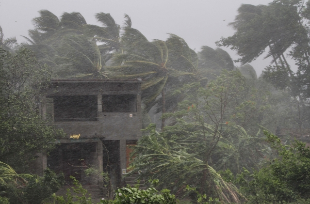 Trees surrounding an abandoned house sway as gusty winds hit ahead of the landfall of Cyclone Fani on the outskirts of Puri, Odisha, on Friday, 3 May 2019.