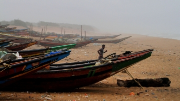 A fisherman runs between the docked fishing boats amid strong winds at in Puri, Odisha, on 2 May.