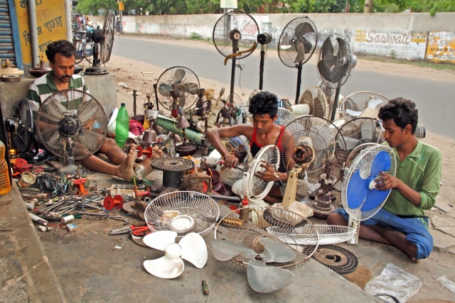 Workers repair fans at a roadside shop during the summer season, at Bolpur in Birbhum district of West Bengal.