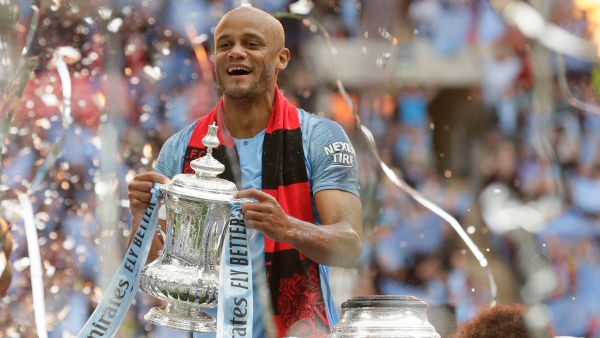 Manchester City's team captain Vincent Kompany lifts the trophy after winning the English FA Cup Final soccer match between Manchester City and Watford at Wembley stadium in London, Saturday, 18 May 2019.