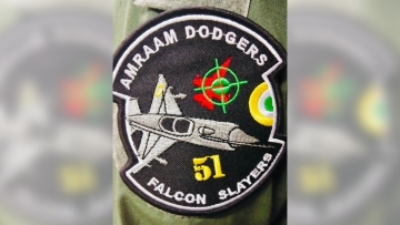 The patch also depicts a MIG-21 Bison in the foreground and a red-coloured F-16 in the background under crosshairs.