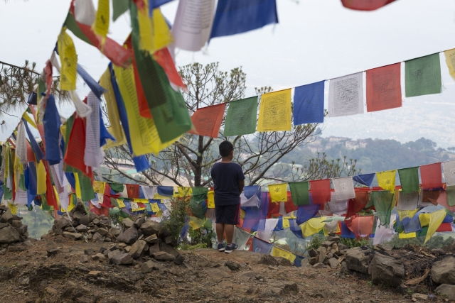 An exile Tibetan boy stands near strings of prayer flags as he waits for his mother in Dharmsala.