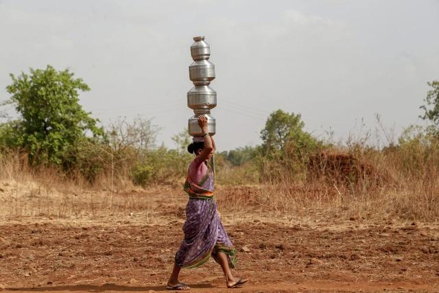 A woman carries multiple pots as she fetches water from a well, in Dhasai village of Thane district. Dhasai, claimed to be among the earliest villages to have implemented cash-less transactions, is facing an acute water shortage as all the wells in the village have dried up.