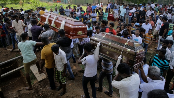 Sri Lankans carry coffins bearing the remains of Berington Joseph, left, and Burlington Bevon, right, who were killed in the Easter Sunday bombings in Colombo, Sri Lanka.