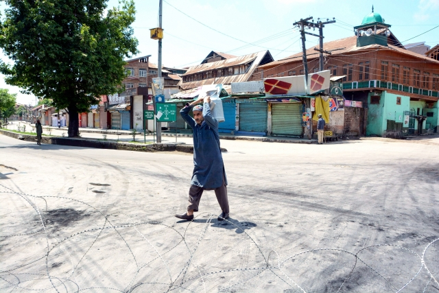 A milkman walks on a deserted road on the second day of curfew imposed to maintain law and order problem following the killing of most wanted militant and Commander-in-Chief of Ansar Gazwatul Hind Zakir Musa, in Srinagar.