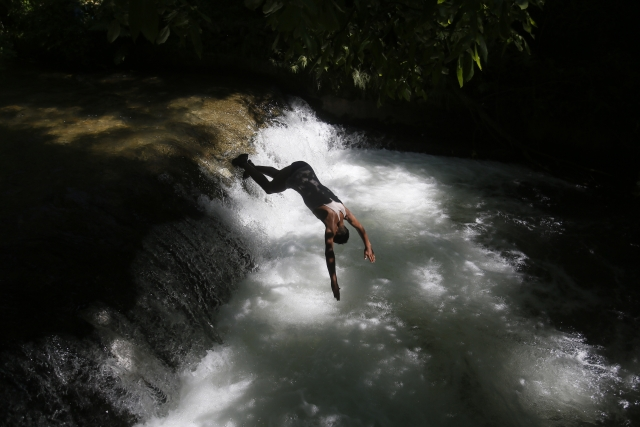 A Kashmiri boy dives into a stream to cool off on the outskirts of Srinagar.