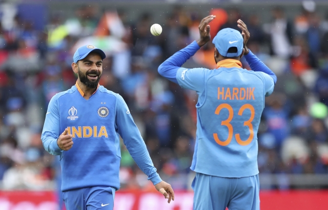 India's captain Virat Kohli, left, smiles as he throws the ball towards his teammate Hardik Pandya during the Cricket World Cup.