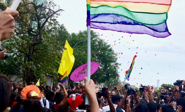 The Pride flag flies high, spreading love and hues.