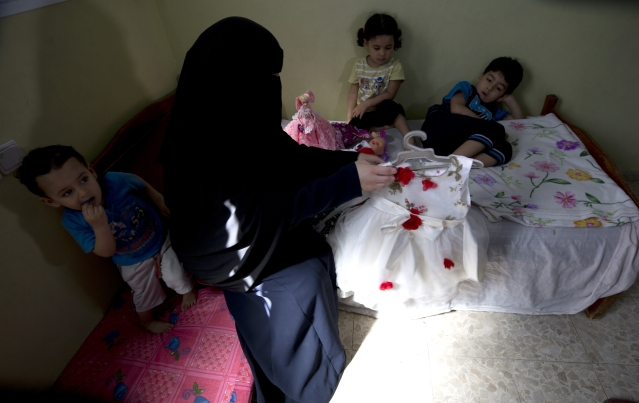 Muna Awad, mother of 5-year-old Aisha a-Lulu, and her children sit on what used to be Aisha's bed at the family home in Burij refugee camp in central Gaza Strip.