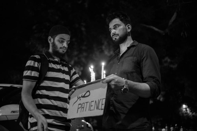 Two men hold candles and a placard reading 'Patience' at the Jantar Mantar protest on Wednesday.