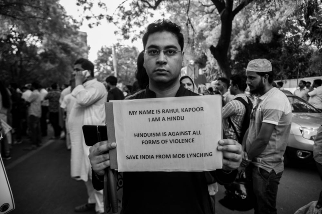 'Hinduism is against all forms of violence,' reads a placard held up by a man at the Jantar Mantar protest on Wednesday.