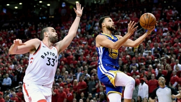 Golden State Warriors guard Stephen Curry (30) drives to the net as Toronto Raptors center Marc Gasol (33) looks on during the NBA Finals.