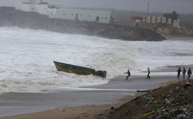 Fishermen try to control their boat amidst rough sea waters at Veraval, in Gir Somnath, Thursday, June 13, 2019.