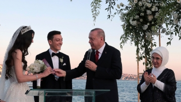 Turkey's President Recep Tayyip Erdogan speaks to Turkish-German soccer player Mesut Ozil and his wife Amine Gulse during a wedding ceremony.