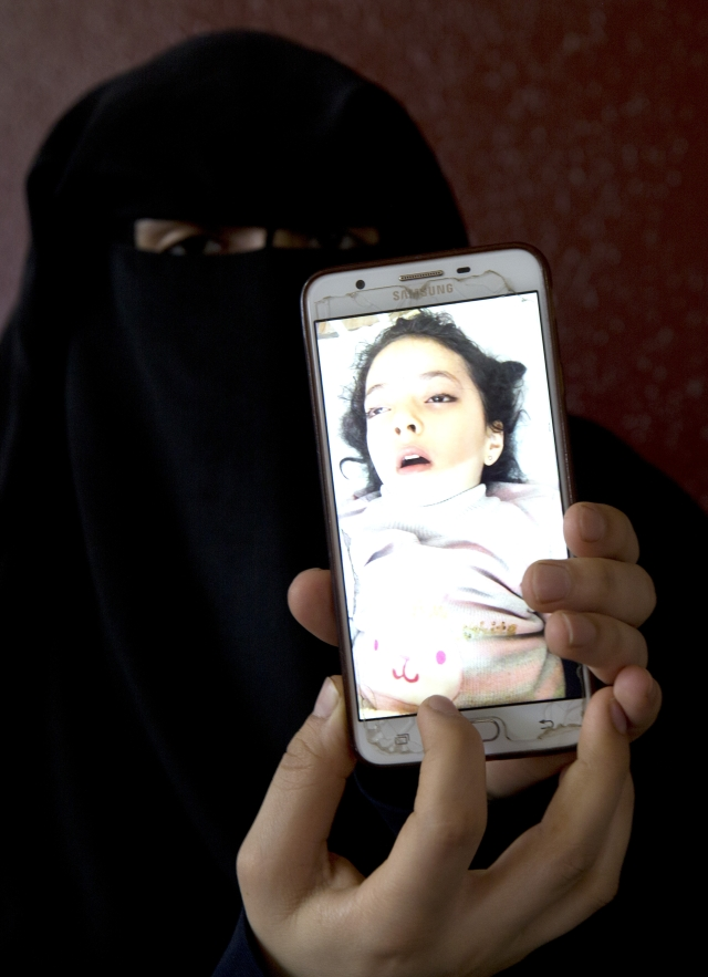 Aisha's mother shows a picture of her daughter in the hospital bed.