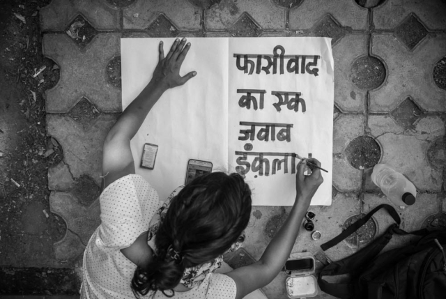 A woman prepares a placard bearing the word 'Fasivaad (Fascism)' at the Jantar Mantar protest on Wednesday, 26 June.