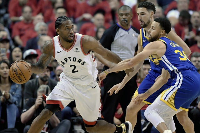 Toronto Raptors forward Kawhi Leonard (2) looks for a way out under pressure from Golden State Warriors guard Stephen Curry (30) and teammate Klay Thompson (11).