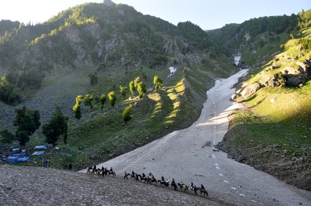 A long shot image of pilgrims mounted on horses enroute to Amarnath.