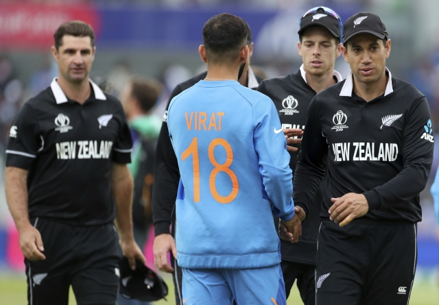 India's captain Virat Kohli, second left, congratulate New Zealand players on their win in the Cricket World Cup semi-final match between India and New Zealand at Old Trafford in Manchester, England, Wednesday, July 10, 2019.