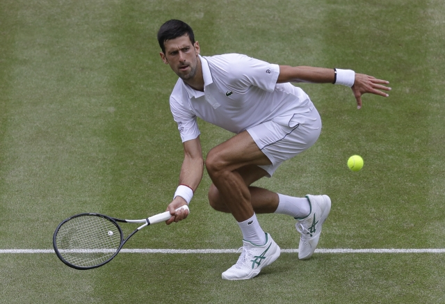 Serbia's Novak Djokovic returns the ball to Belgium's David Goffin during a men's quarterfinal match on day nine of the Wimbledon Tennis Championships in London.