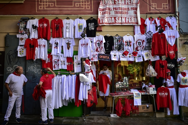 Three men dressed in white and red clothes stand beside San Fermin's shop at the San Fermin Festival, in Pamplona, northern Spain.