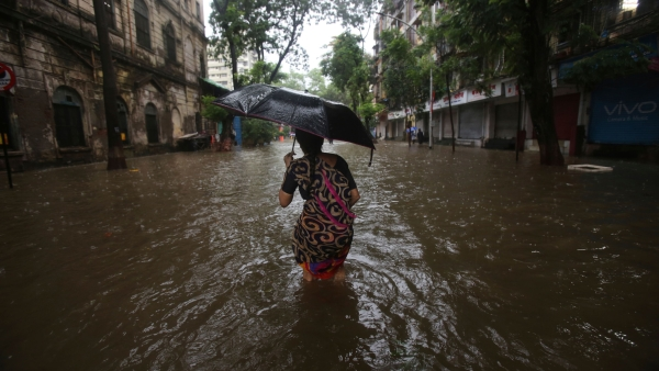 A woman walks in the middle of a waterlogged street in Mumbai.